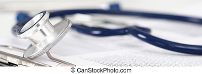 Stethoscope head lying on medical form on clipboard pad