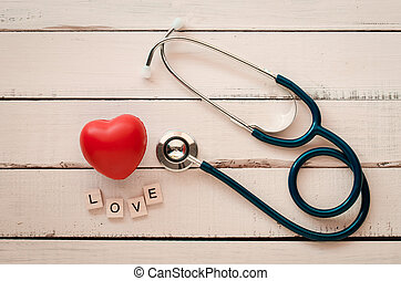 "stethoscope heart and the word ""love""on wooden floor"