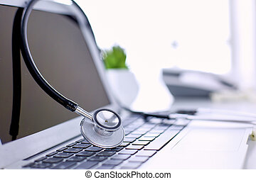 Stethoscope lying on a laptop keyboard in a concept of online medicine or troubleshooting the computer viewed low angle with copy space