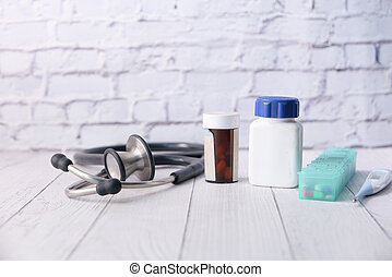stethoscope, medicine container and pills on wooden background