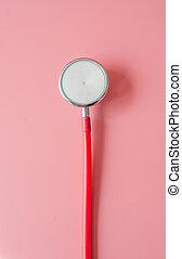 Stethoscope on pink background.