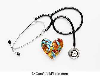 stethoscope on white background with pills in shape of heart