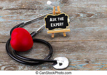 Stethoscope with red heart and blackboard with a text: ask the expert on wooden background