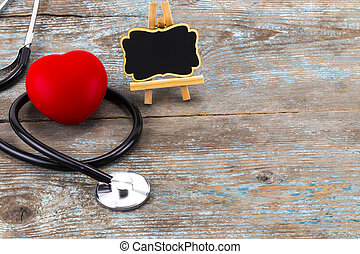 Stethoscope with red heart and blackboard with empty space for a text on wooden background