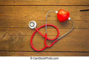 Stethoscope with red heart on a wood background.