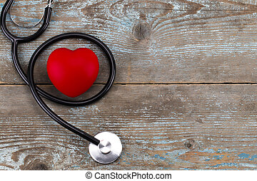 Stethoscope with red heart on a wood background,with copy space
