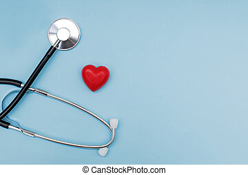Stethoscope with red heart on blue background with copy space.