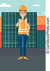 Stevedore standing on cargo containers background. - A woman...