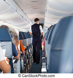 Interior of airplane with passengers on seats and steward walking the aisle.