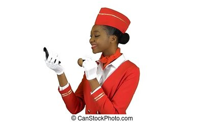 Stewardess afro american looks in the mirror and paints her face with blushes. Alpha channel