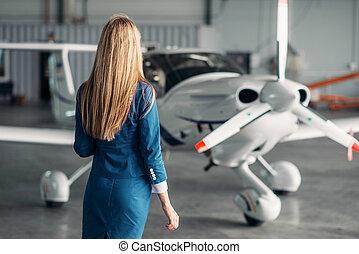 Stewardess against turboprop airplane in hangar - Attractive...