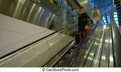 Stewardess and passenger with luggage go down the escalator.