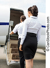 Stewardess And Pilot Boarding Private Jet - Rear view of...