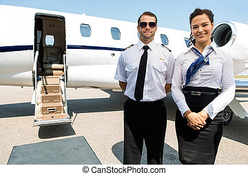 Stewardess And Pilot Standing Against Private Jet - Portrait...