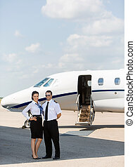 Stewardess And Pilot Standing Together Against Private Jet -...