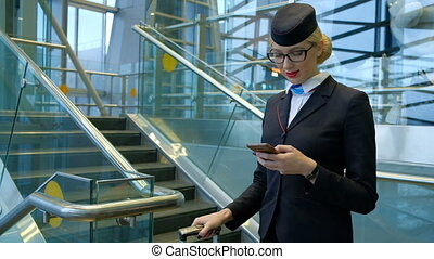 Stewardess at the airport with a phone in her hands helps passenger.