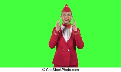 Stewardess crossed her fingers on both hands in the hope of success. Green screen