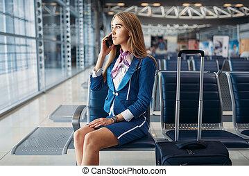 stewardess, falando, por, telefone móvel, em, aeroporto
