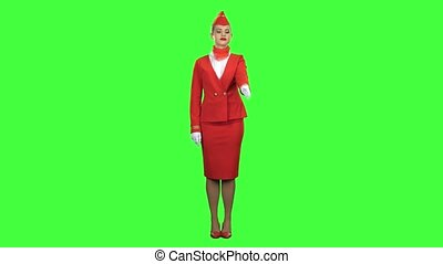 Stewardess gestures where the emergency exit is. Green...