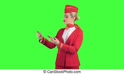 Stewardess girl in a red suit is picking up the credit card code. Green Screen