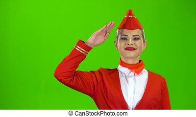 Stewardess in a red suit salutes the pilot. Green screen