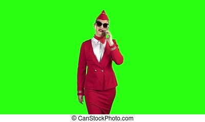 Stewardess in a red suit speaks on the phone and steps away . Green screen. Slow motion