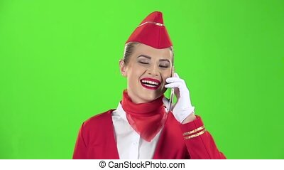 Stewardess in a red suit speaks on the phone . Green screen. Slow motion
