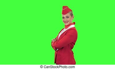 Stewardess in a red suit winks a slight flirt. Green screen....