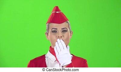 Stewardess in a red suit winks a slight flirt sends an air...