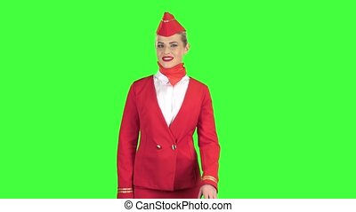 Stewardess in a red suit winks a slight flirt sends an air kiss. Green screen