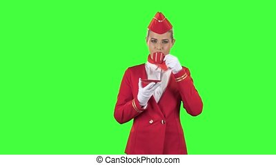 Stewardess in gloves drinks coffee with a red mug. Green...
