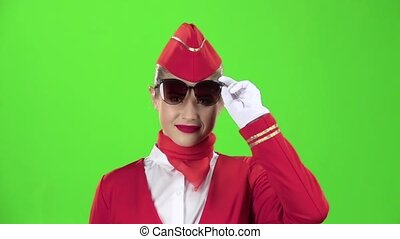 Stewardess in sunglasses a red suit winks a slight flirt...