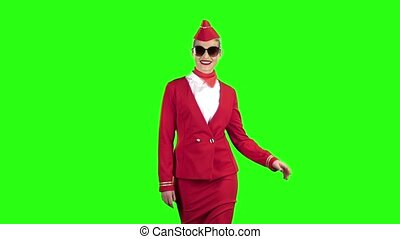 Stewardess in sunglasses goes and winks flirting. Green...