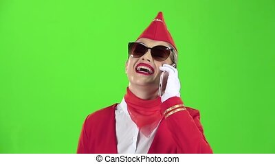 Stewardess in sunglasses in a red suit speaks on the phone . Green screen. Slow motion