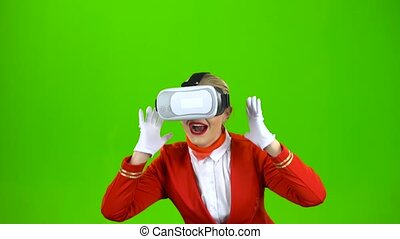 Stewardess in the glasses of virtual reality plays games. Green screen
