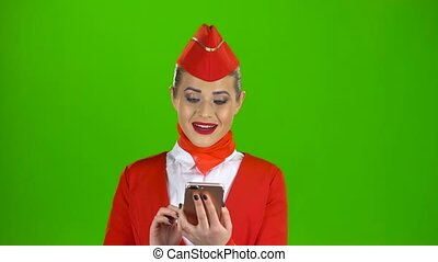 Stewardess in the red attire looks into the phone and is...