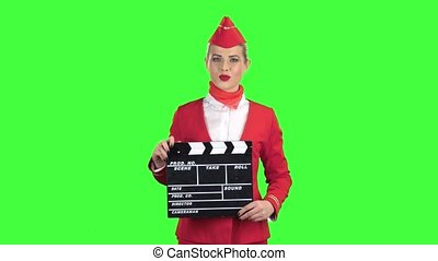 Stewardess is holding a clapperboard in her hands. Green...