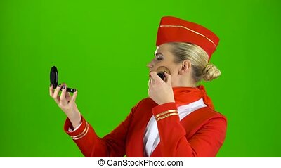 Stewardess looks in the mirror and paints her face with a tassel. Green screen