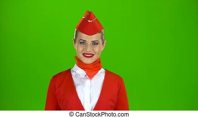 Stewardess in a red outfit raises her head and smiles looks into the distance. Green screen