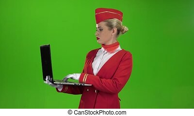 Stewardess prints the text on the laptop. Green screen