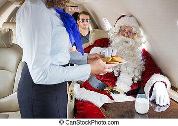 Stewardess Serving Cookies To Santa In Private Jet