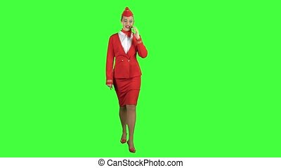 Stewardess speaks on the phone and paces into the distance. Green screen.