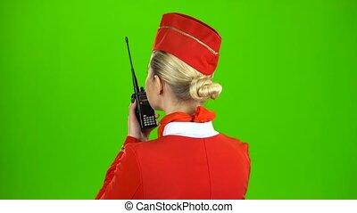 Stewardess speaks on the walkie talkie. Green screen. Back view
