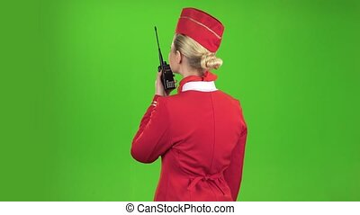 Stewardess speaks on the walkie talkie. Green screen. Back view