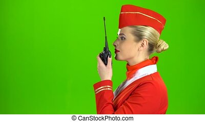 Stewardess in a red suit speaks on the walkie talkie and smiles. Green screen. Side view