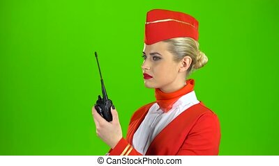 Stewardess in a red suit speaks on the walkie talkie and smiles. Green screen