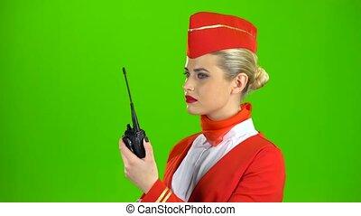 Stewardess speaks on the walkie talkie. Green screen