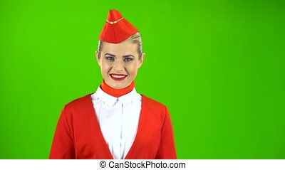 Stewardess in a red suit steps and winks a slight flirt. Green screen