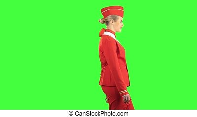 Stewardess steps forward and looks in front of her. Green screen. Side view