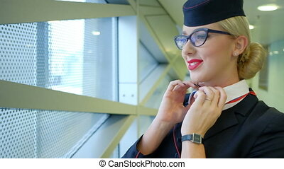 Stewardess with glasses corrects scarf and puts his hand to his head.